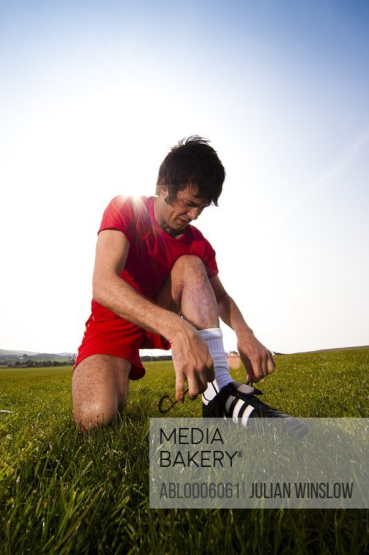 Soccer player tying shoelaces