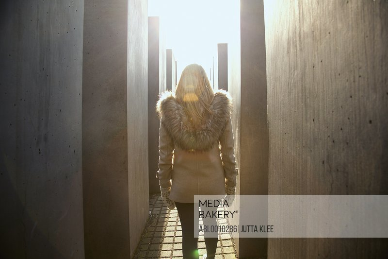 Back View of Young Woman Walking along the Concrete Steles of the Holocaust Memorial, Berlin, Germany