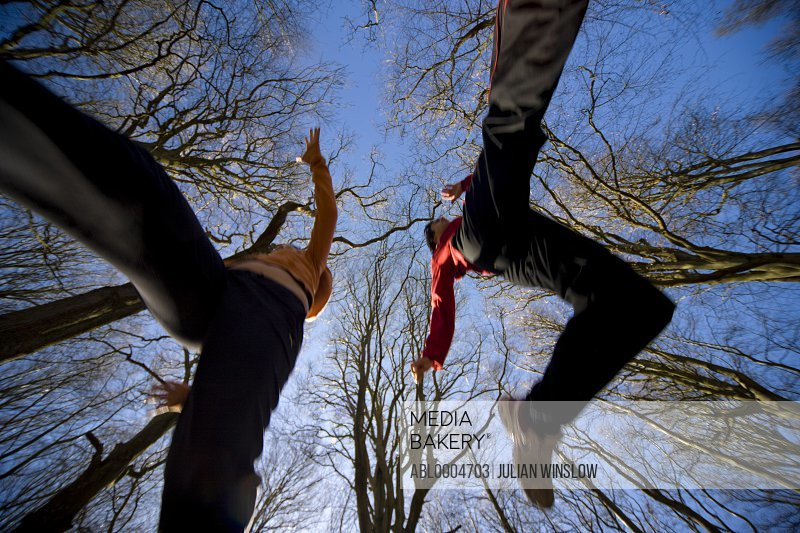 Two people jumping mid air with trees and blue sky