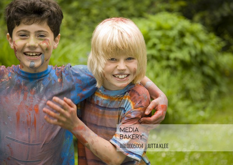 Two young boys covered in watercolor paint laughing in a garden