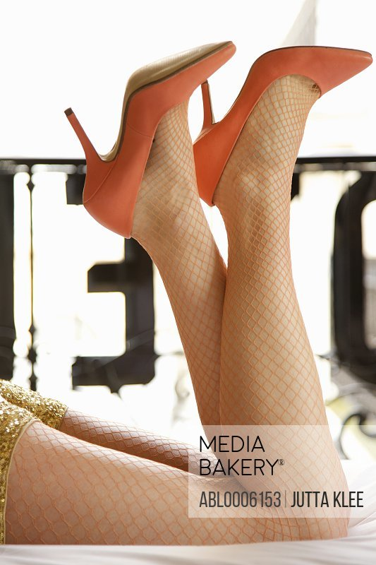 Woman's legs with fishnet stockings and high heels shoes