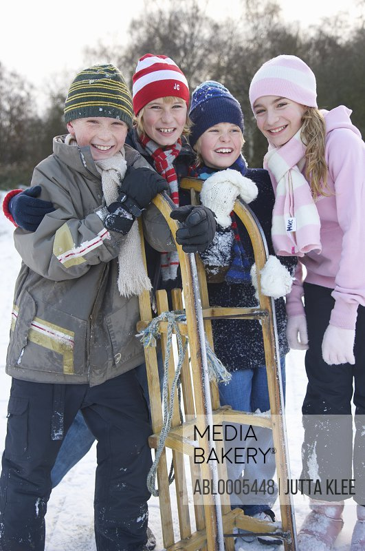 Smiling children leaning on a sled