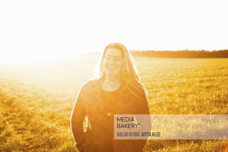 Woman Standing in a Field Smiling