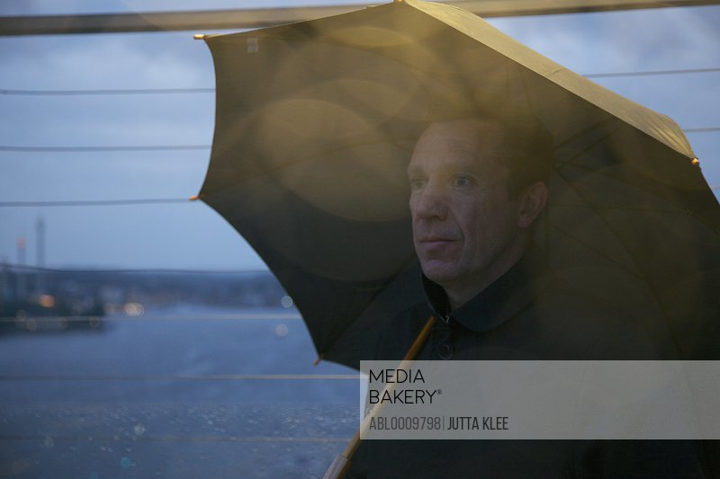 Portrait of Man on Observation Deck under Umbrella