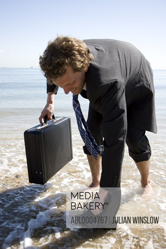 Young businessman on a beach holding briefcase and picking up shoes from water edge