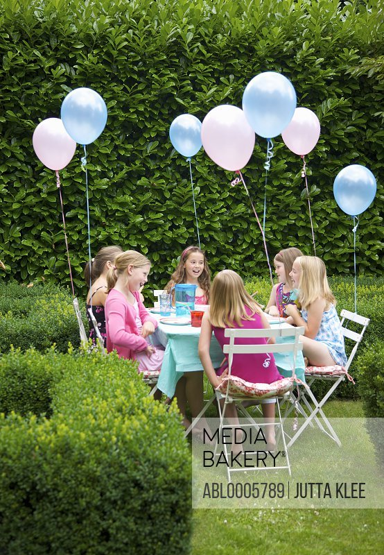Group of young girls having a party in a garden smiling and laughing