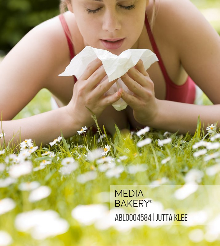 Young woman lying on stomach on the grass sneezing