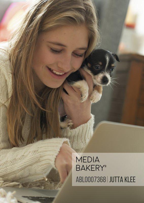 Teenage Girl Hugging Puppy whilst Using Laptop
