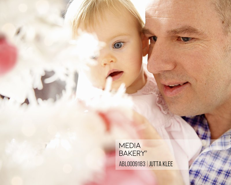 Father and Baby Daughter Looking at Christmas Tree, Close-up view