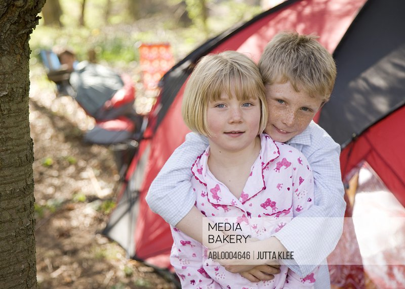 Portrait of boy and girl embracing outside tent at campsite