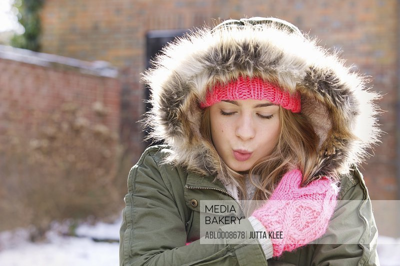 Teenage Girl Wearing Parka Hugging Herself Outdoors