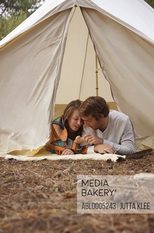 Young couple lying in a tent entrance