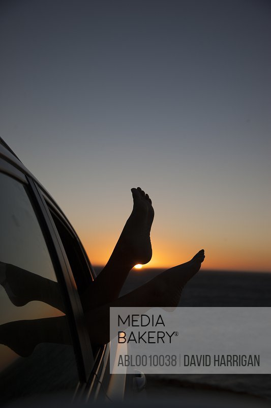 Woman's Feet Sticking out of Car Window at Sunset