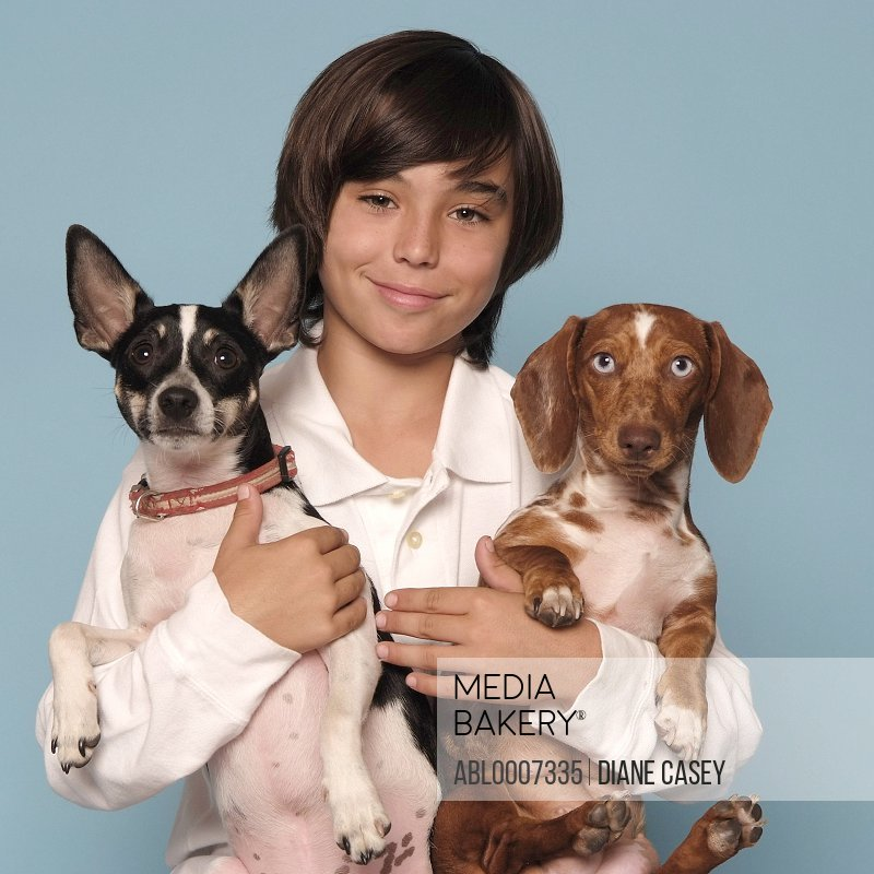 Boy Holding Two Dogs in his Arms