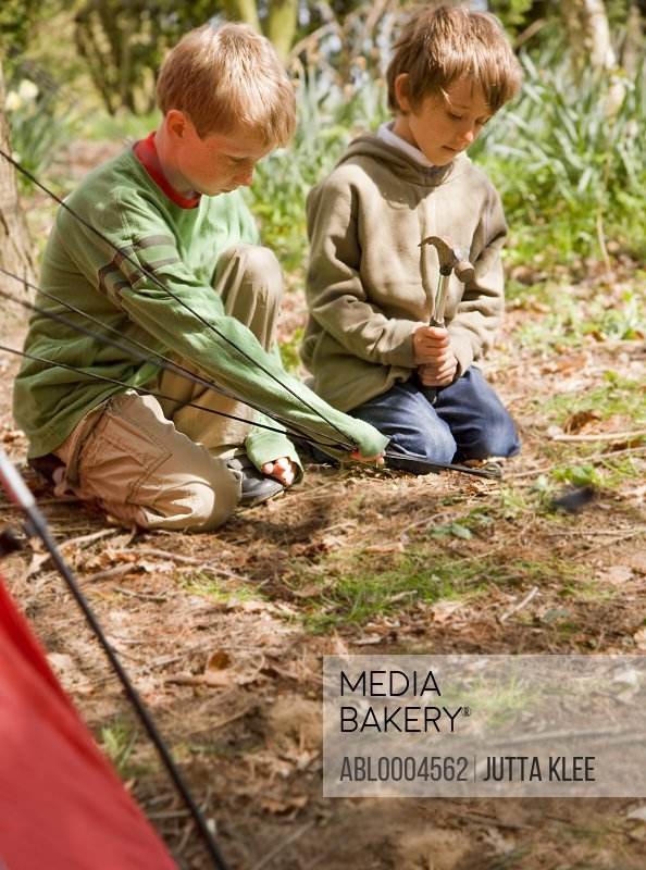 Portrait of two boys building a tent