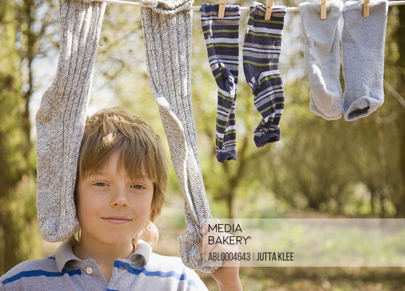 Close up of boy standing between socks hanging from clothes line