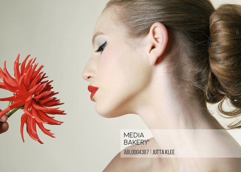 Young woman holding red dahlia