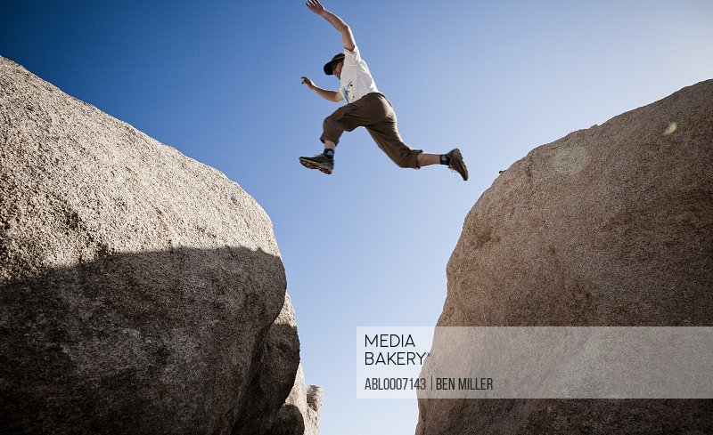 Man Leaping between Two Boulders