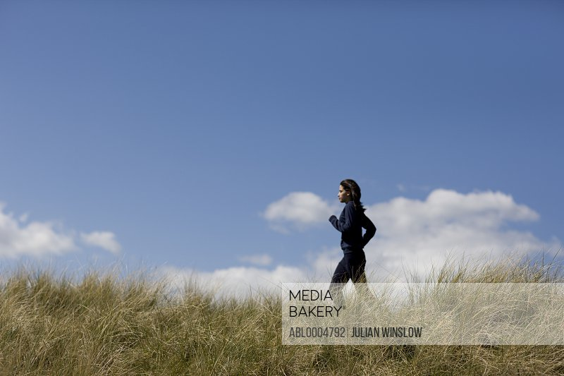 Young woman running through sand dunes