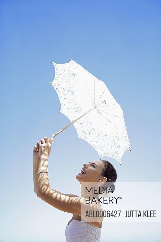 Bride Holding Parasol against Blue Sky