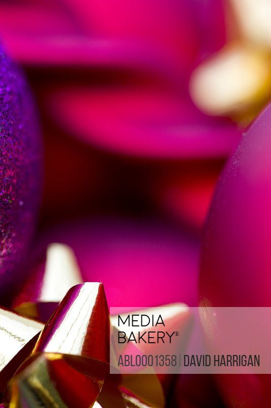 Extreme close up of red and purple Christmas baubles and a gold bow