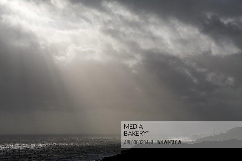 Grey sky with sun rays and thunder