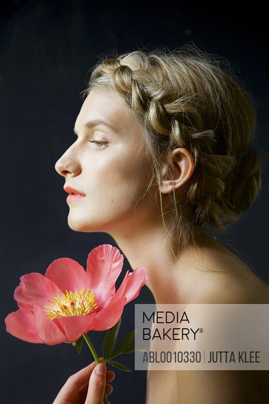 Profile of Young Woman with Braided Hair Holding Peony
