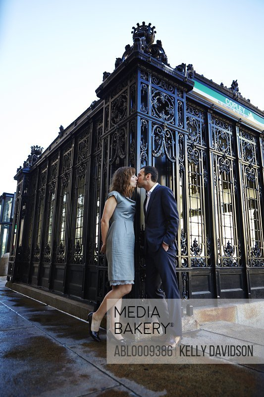 Couple Kissing next to Wrought Iron Building