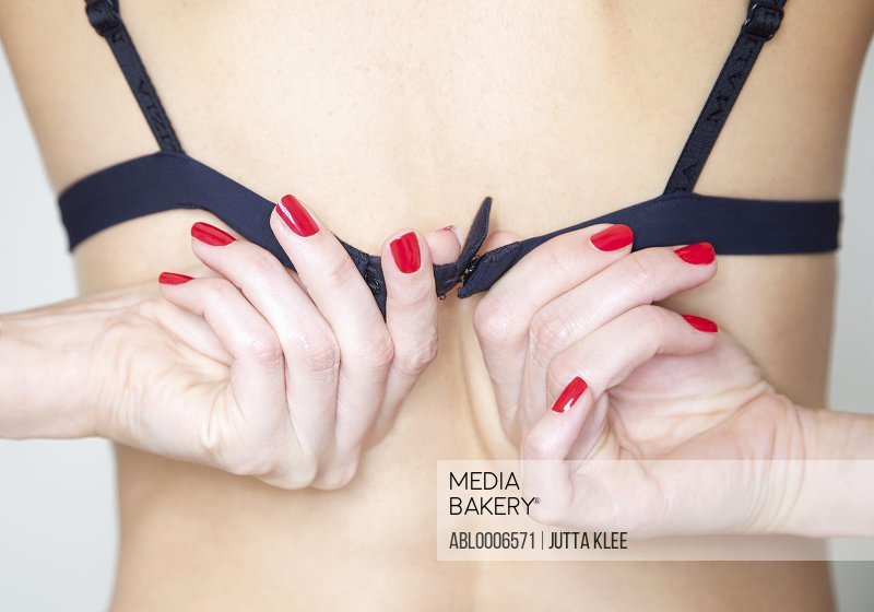 Close up of Woman's Hands with Red Nail Polish Fastening Bra - Back view
