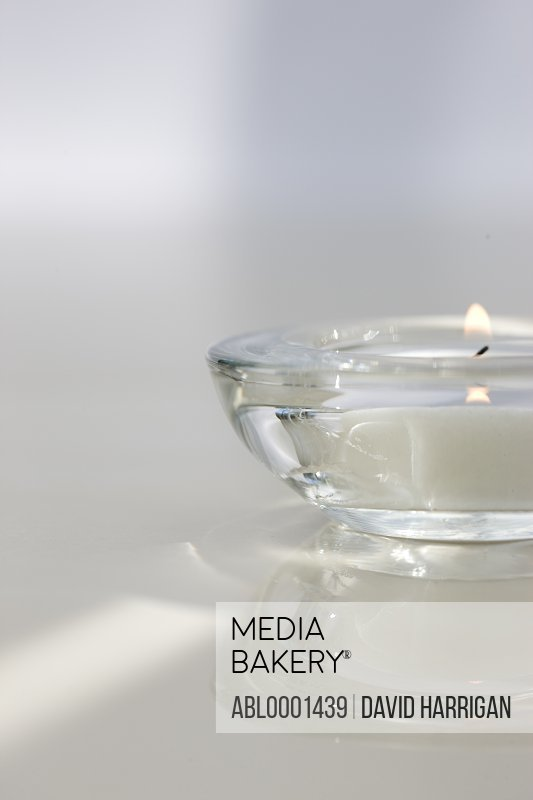 Close up of a burning tea light in a transparent glass holder