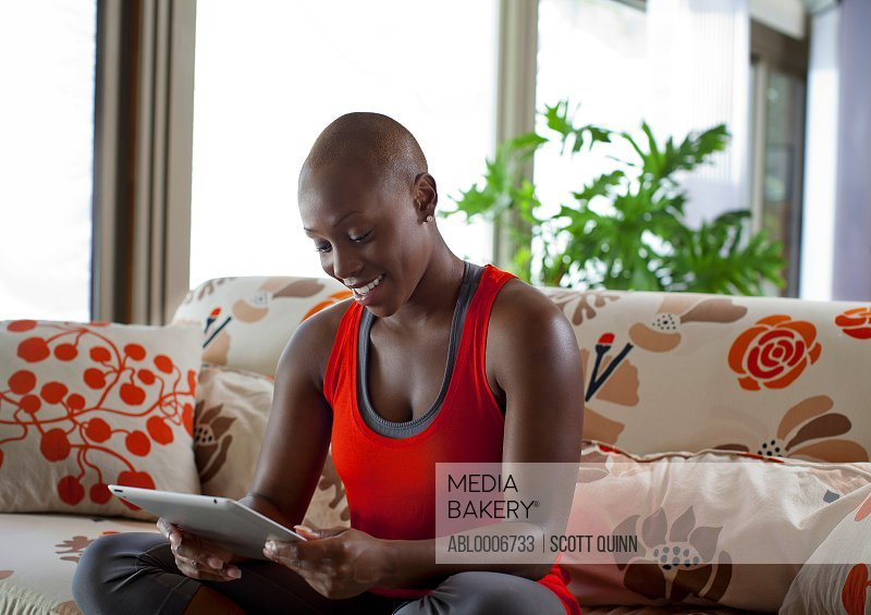 Woman Sitting on Sofa Holding Tablet PC