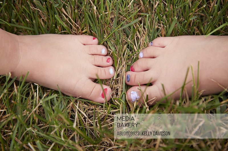 Young Girls Feet with Painted Toenails on Grass