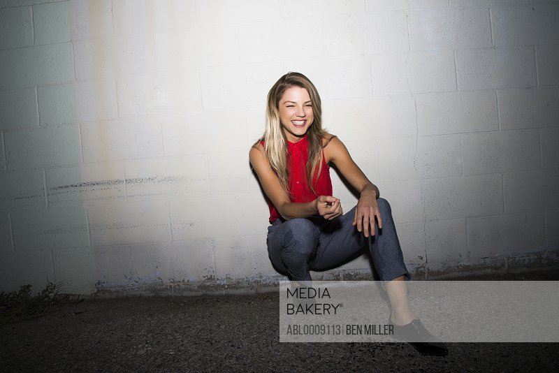 Smiling Woman Crouching against Wall