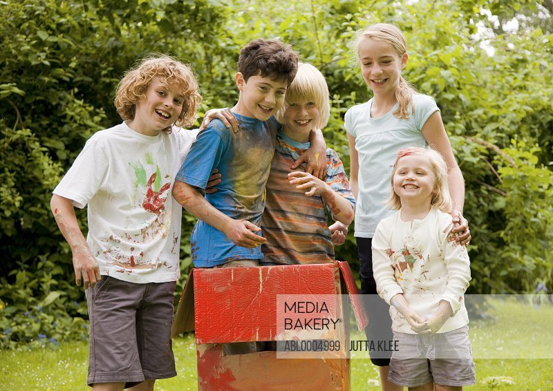 Children covered in watercolor paint in a garden, two of them standing in a cardboard box