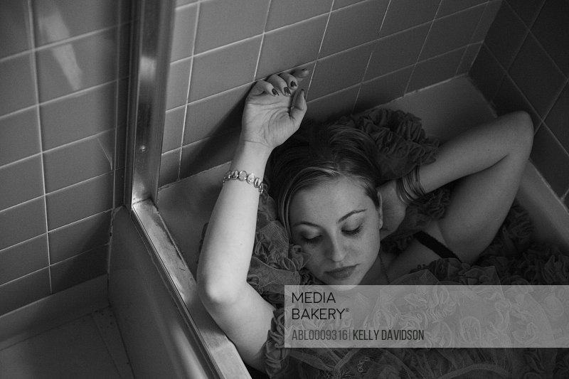 Woman Lying in Bathtub Wearing Ruffle Dress