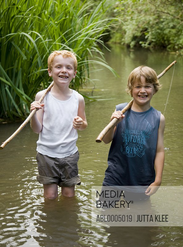 Two young boy standing in a river laughing and holding wooden sticks