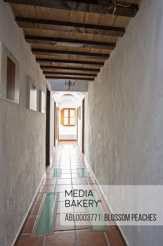 Empty Corridor with Tiled Floor and Exposed Beams