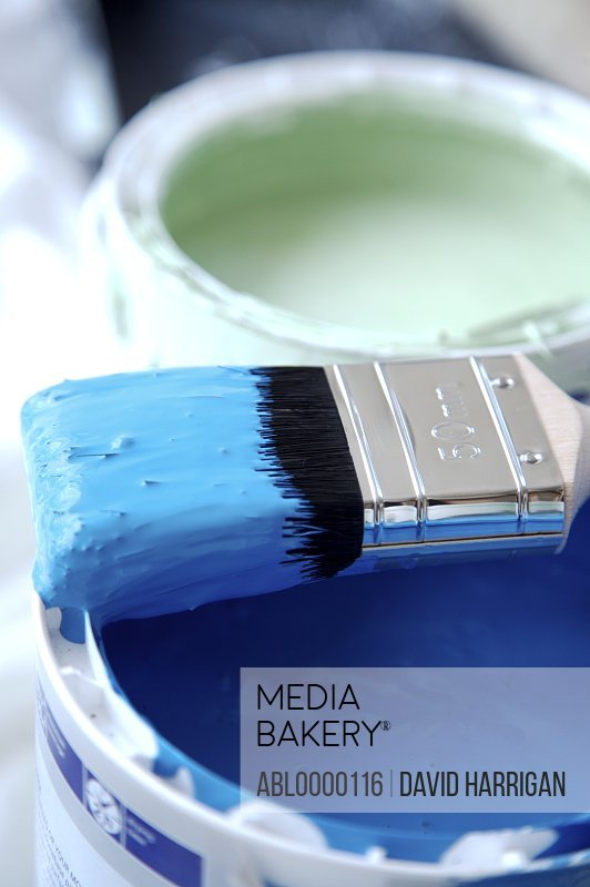 Close up of blue paint pot and paintbrush