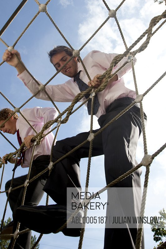 Two businessmen at an obstacle course climbing a cargo net