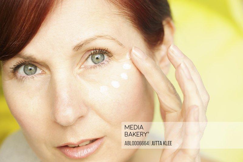 Woman Applying Moisturizing Cream on Face