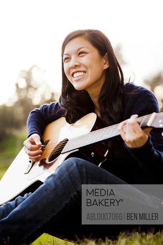 Young Woman Playing Guitar Outdoors