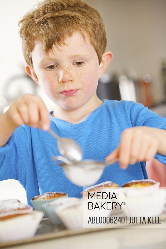 Young boy sprinkling cupcakes with icing sugar