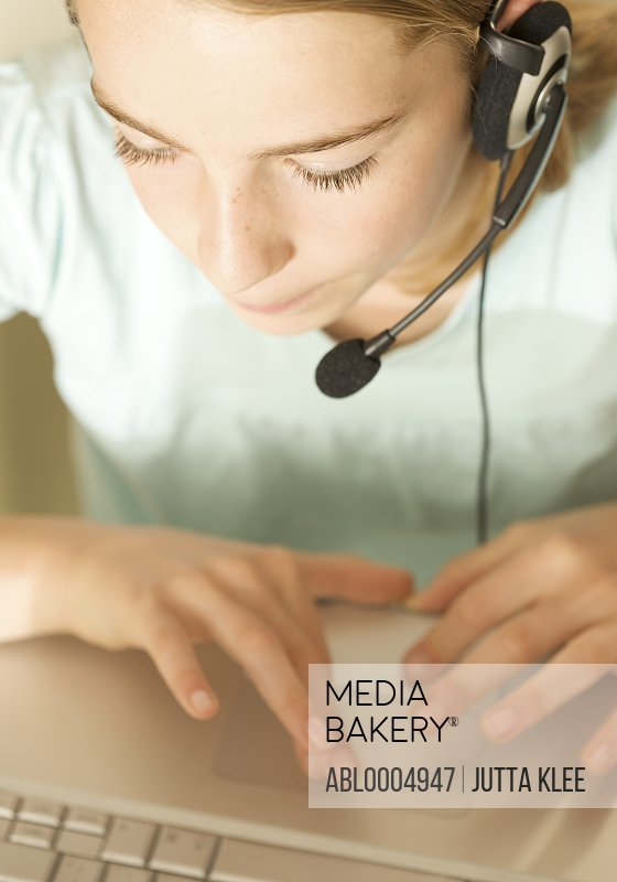 Close up of smiling girl wearing earphones and microphone typing on a laptop