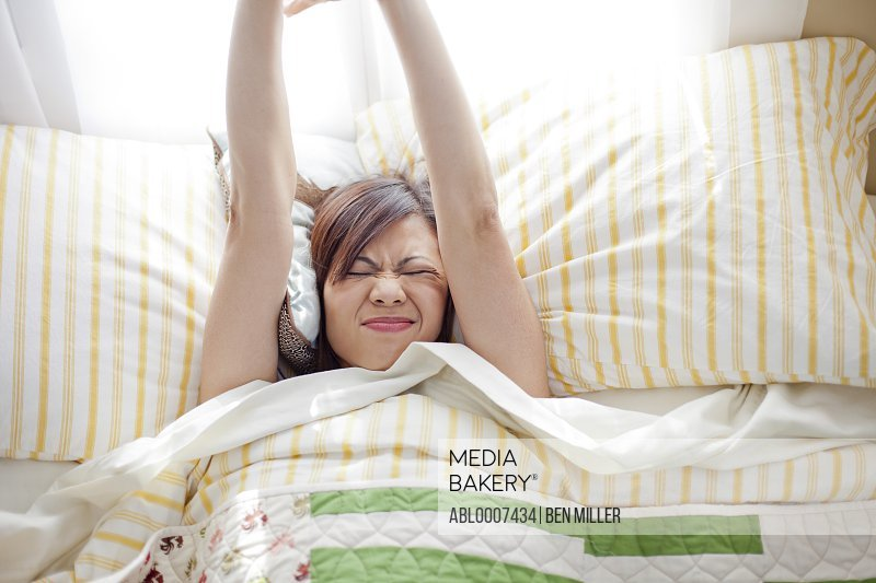 Woman in Bed Stretching Arms