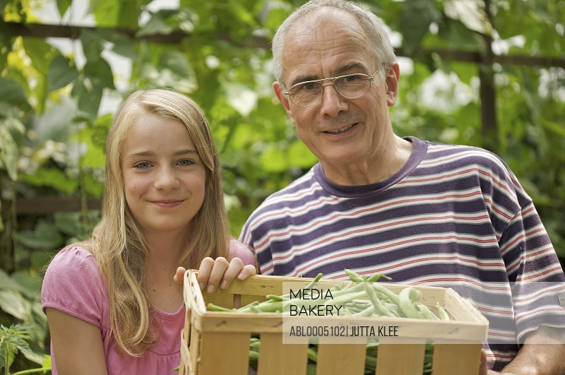 Young girl and mature man holding a crate of broad beans