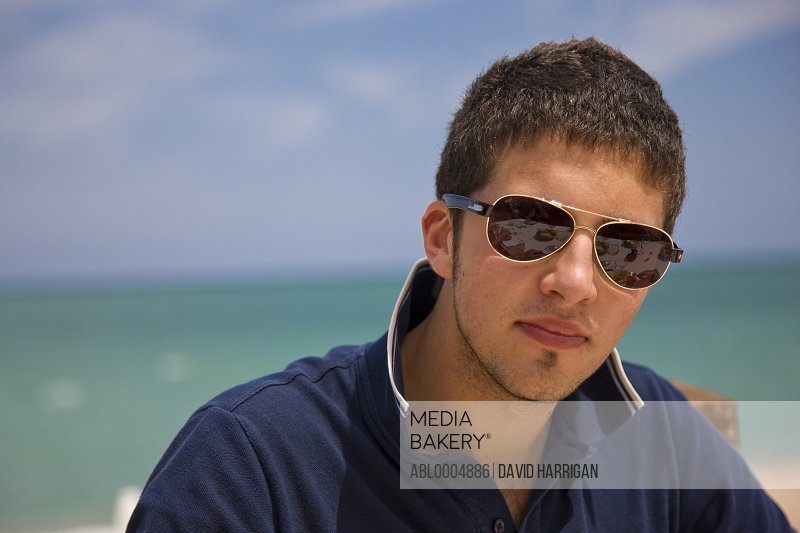 Close up of a young man with sunglasses by the sea