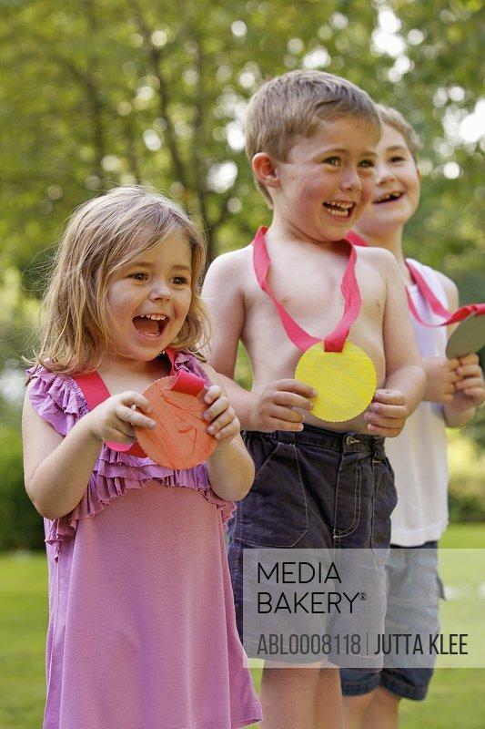 Smiling Children Holding Cardboard Medals