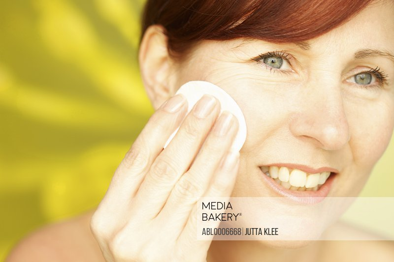 Smiling Woman Using Cotton Pad on Face