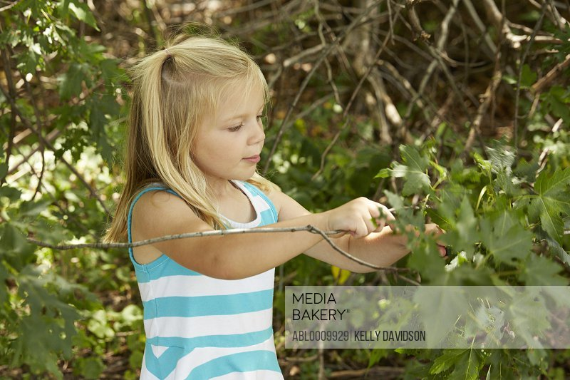 Young Girl Playing in Garden Holding Twig with Leaves
