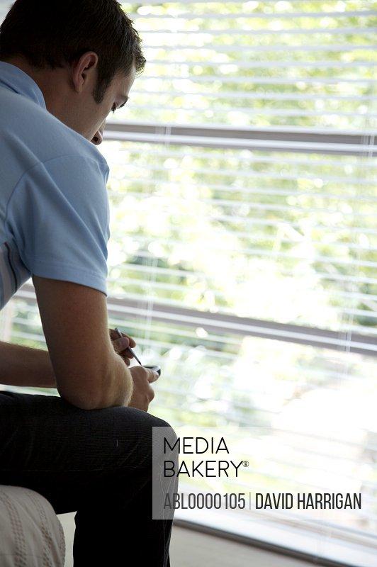Man communicating with hand held PDA facing window